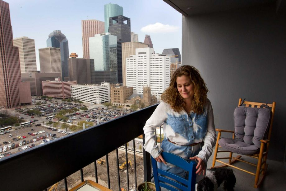 Woman arranging patio furniture on the balcony of her downtown apartment